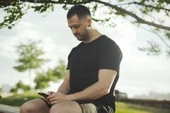 Close up of young man typing text message on mobile phone outdoors in the park. Close up of young man in black sportswear typing text message on mobile phone Stock Photo