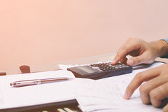Close up young man with calculator counting at home with copy space, Royalty Free Stock Image