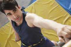 Close-up of young man climbing up a climbing wall in an indoor climbing gym, directly above Royalty Free Stock Photography