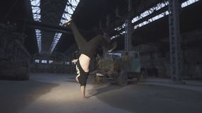 Close up of young man dancing breakdance in an abandoned building. Caucasian guy jumping on his hand indoor. Concept of. Healthy active lifestyle. Slow motion stock video footage