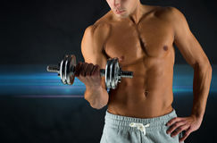 Close up of young man with dumbbell flexing biceps. Sport, bodybuilding, training and people concept - close up of young man with dumbbell flexing biceps over Royalty Free Stock Photo