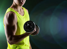 Close up of young man with dumbbell flexing biceps Royalty Free Stock Image