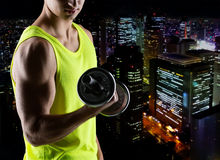 Close up of young man with dumbbell flexing biceps. Sport, bodybuilding, training and people concept - close up of young man with dumbbell flexing biceps over Royalty Free Stock Photos