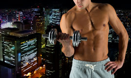 Close up of young man with dumbbell flexing biceps. Sport, bodybuilding, training and people concept - close up of young man with dumbbell flexing biceps over Stock Image