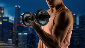 Close up of young man with dumbbell flexing biceps. Sport, fitness, weightlifting, bodybuilding and people concept - close up of young man with dumbbell flexing Stock Image