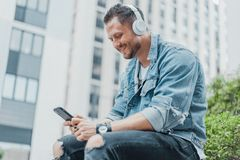 Close up of young man in earphones and looking at mobile phone. stock image