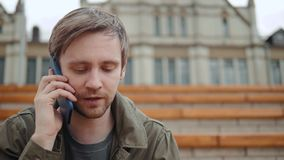 Close up of a young man enjoying talking on a mobile phone in park grass field tourist student. stock video footage