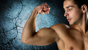 Close up of young man flexing and showing biceps Royalty Free Stock Photography