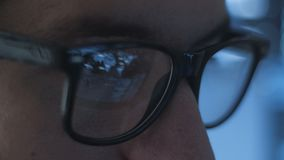 Closeup of young man geek programmer in glasses working late at office, closeup eyes of male hacker working in data