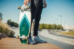 Close up of young man holding longboard or skateboard in the park. royalty free stock photography