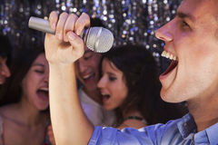 Close- up of young man holding a microphone and singing at karaoke, friends singing in the background Stock Images