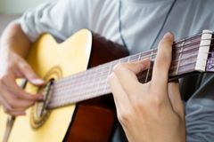 Close up of young man playing guitar. stock photos
