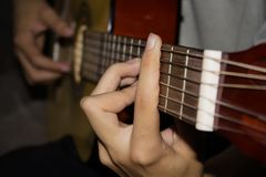 Close up of young man playing guitar. royalty free stock images