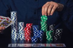 Close up of young man poker player hands showing cards and taking chips at the casino table. Gambling tournament winner royalty free stock photos