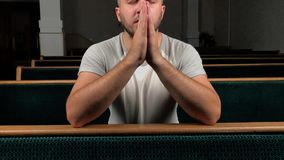 Close up of young man praying to god. Concept of faith and religion.  stock video footage
