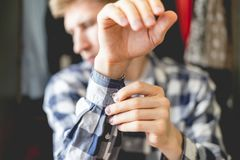Close up young man put on casual shirt at home, adjusting a button an the sleeve close up f royalty free stock photos