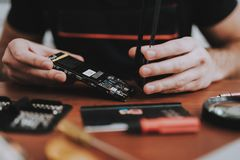 Close up Young Man Repairing Mobile Phone at Table stock image