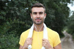 Close Up Of Young Man Running In Park Listening To Music Holding a Towel Stock Images