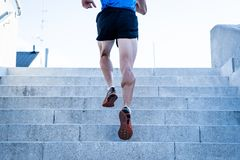 Close up of young man running up the stairs with running clothes stock photo