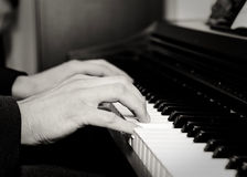 Close-up of a young man's hands playing a piano Stock Image