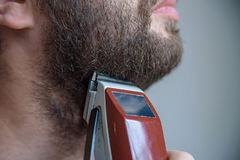 Close up young man shaving with electric razor Stock Photo