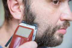 Close up young man shaving with electric razor Royalty Free Stock Photo