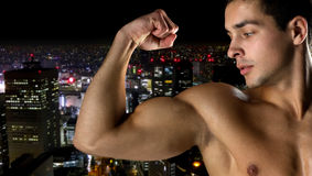 Close up of young man showing biceps. Sport, bodybuilding, strength and people concept - close up of young man showing biceps over night city background Stock Photos