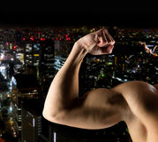 Close up of young man showing biceps. Sport, bodybuilding, strength and people concept - close up of young man showing biceps over night city background Royalty Free Stock Images