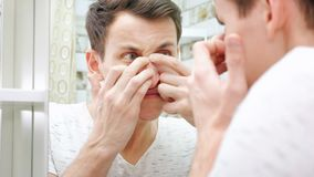 Close up of young man standing close to a mirror in the bathroom and squeezing a pimple on his face royalty free stock image