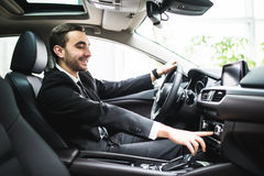 Close up of young man in suit driving car and switching some button on panel of car stock photos
