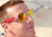 Close up of young man with sunshades reflecting  in sunglasses Royalty Free Stock Photography