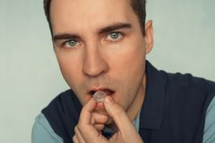 Close - up of a young man with a tablet in his hands to freshen his breath.  Royalty Free Stock Photo