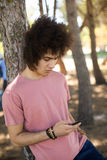 Close up of young man using mobile phone at forest. Close up of young man using mobile phone while leaning on tree trunk at forest Royalty Free Stock Images