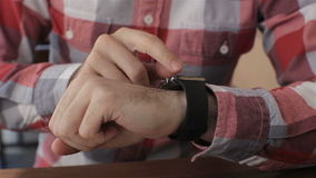 Close up of young man using smartwatch while sitting in cafe stock video footage