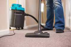 Close up a young man vacuuming Stock Images