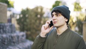 Close up of a young man in a beanie talking on phone outside. Close up of a young man wearing a dark green vest and a beanie standing in a park and talking on stock video footage