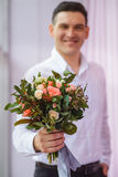 Close up of young man in white shirt giving bouquet of flowers as surprise, focus on roses. Close up of young man in white shirt giving bouquet of flowers as Royalty Free Stock Photography