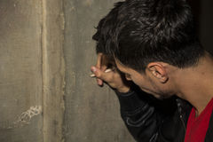 Close-up of young man writing on stone wall with pencil Royalty Free Stock Photography