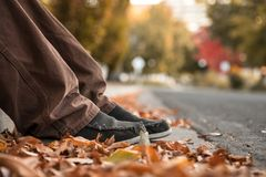 Close Up Of Young Mans Feet In Autumn Leaves on Ground By Curb. Close Up Of Young Mans Feet In Autumn Leaves on Ground By Curb In City Street. Selective Focus Stock Photos