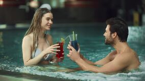 Closeup of young couple resting in pool . Happy man and woman drinking cocktails