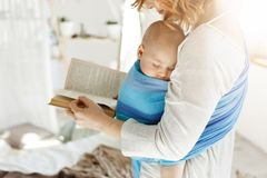 Close up of young mom reading fairy tales for her newborn little son in comfortable light bedroom. Baby falls asleep. While she was reading Royalty Free Stock Photos