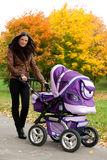 Close-up young mother with stroller. In autumn of city park Stock Photography