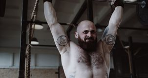 Close-up young muscular Caucasian sportsman exercising with heavy weight crossbar in large hardcore gym slow motion. Professional male athlete training stock video
