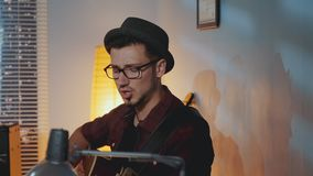 Close-up of young musician singing into microphone and playing the guitar in home recording studio stock video footage