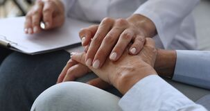 Empathic young nurse holding hand supporting elderly patient.