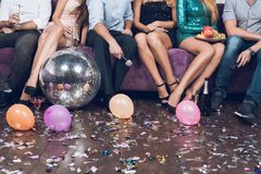 Close up. Young people rest in pairs in a nightclub. They are sitting on a large lilac sofa. Royalty Free Stock Images