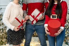 Close up of young people in sweaters holding gifts royalty free stock images