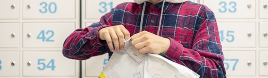 Close up young person quickly unpackage the recieved delivery in post office, mail boxes on background f stock photo