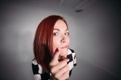 Close up of young pretty lady in black and white blouse looking at camera and holding her finger up. Beautiful woman with red hair and brown eyes looking stock photo