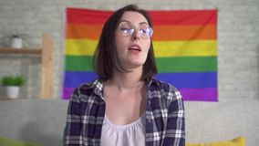 Close up young pretty woman blogger in the shirt on the background of the flag of the LGBT records video. Close up young pretty woman blogger in the shirt and stock video footage